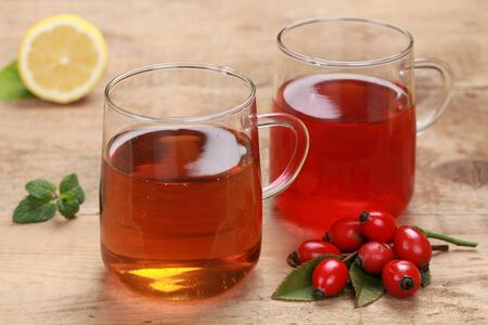 Rooibos and rosehip tea in glasses on a wooden table