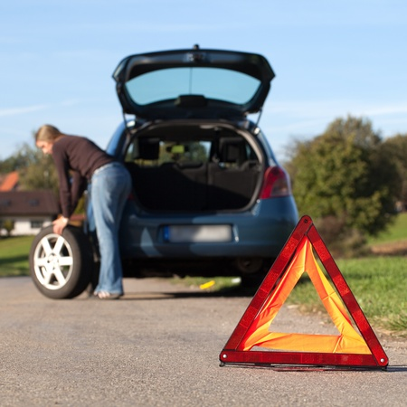 flat tyre: Changing the tire on a broken down car on a road with red warning triangle Stock Photo
