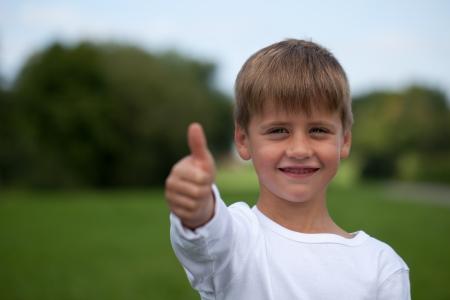 Little boy showing thumbs up, plenty of copyspace photo
