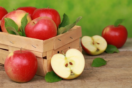 Apples with leaves in a wooden box on a table with green background Stock Photo - 17078550