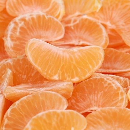 Het verzamelen van mandarijnen gesneden in stukken en de vorming van een achtergrond