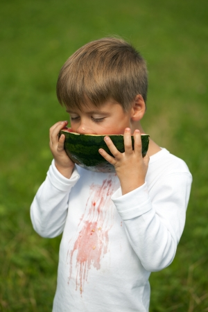 Little boy eating a watermelon and gets stains on his T-shirt photo