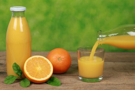 Fresh orange juice is pouring from a bottle into a glass Stock Photo - 17078528