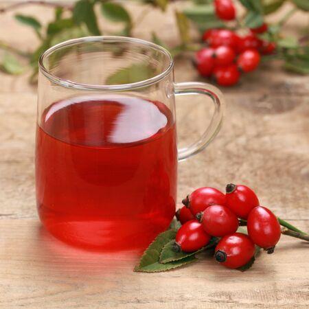 Rozenbottel thee in een glas op een houten tafel Stockfoto