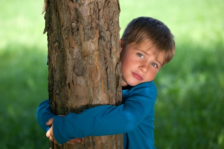 Symbolic picture: Little boy embracing a tree
