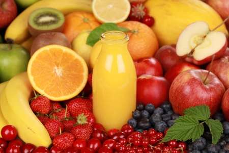 Orange juice in a bottle surrounded by fresh fruits  photo