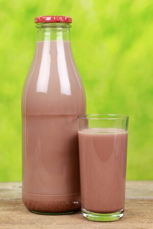 milk chocolate: Chocolate milk in a bottle and in a glass on a wooden table