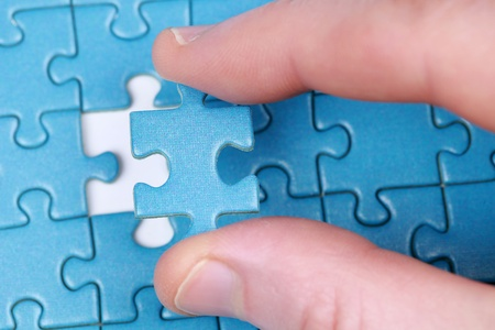 Fingers putting the last piece of puzzle in place Stock Photo - 17304581