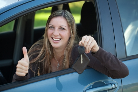 A smiling woman is leaning out of the window and showing a key Stock Photo - 17282749