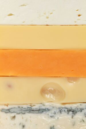 emmental: Different types of cheese such as Gouda, Cheddar and Gorgonzola forming a background
