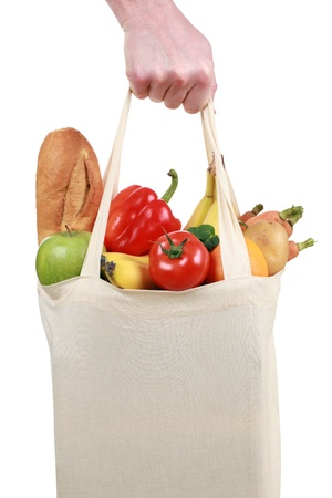 Hand holding a shopping bag filled with groceries such as fruits and vegetables, isolated on white