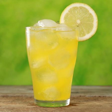 cubos de hielo: Limonada fr�a de naranja en un vaso con cubitos de hielo, servido con una rodaja de lim�n