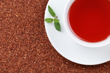 rooibos tea: Rooibos Tea in a cup with lots of copy space and a lemon balm leaf