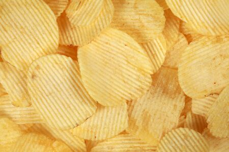 potato chips: Collection of rippled potato chips forming a background