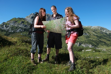 Group of young people reading a map in the mountains while hiking photo
