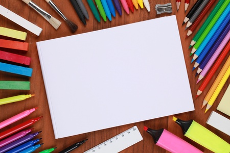 teaching crayons: Empty notebook with copyspace, surrounded by crayons, pencils and other school equipment Stock Photo