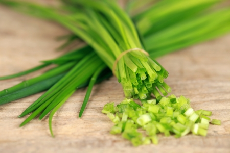 Chopped chives on wooden board, shallow depth of field