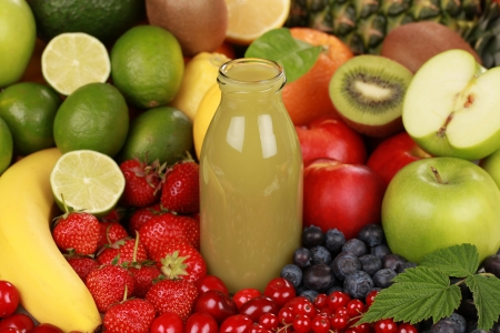 A bottle of kiwi and green apple smoothie surrounded by fruits photo