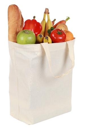 Herbruikbare boodschappentas gevuld met een brood, groenten en fruit, geïsoleerd op wit Stockfoto