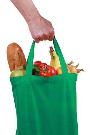 Mano que sostiene una bolsa llena de comestibles, aislado en blanco