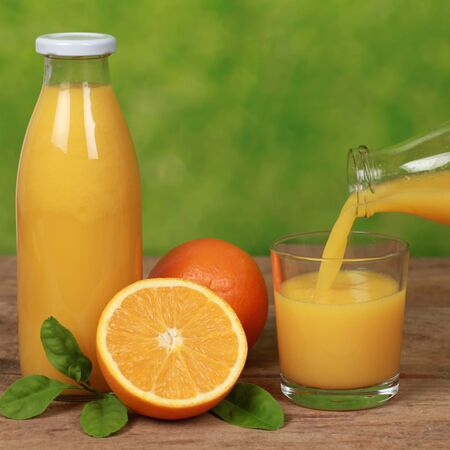 Oranges and fresh juice is pouring from a bottle into a glass on a wooden table Stock Photo - 18131421