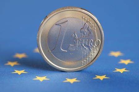european union currency: One Euro coin on the European Union flag