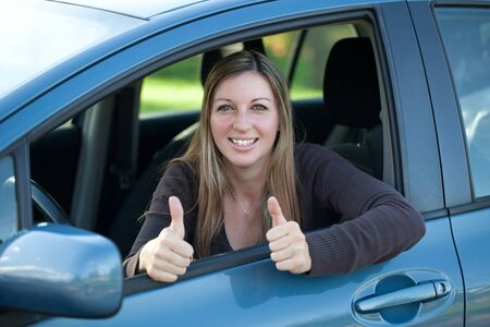 A successful driver looking out of the window and showing thumbs up photo