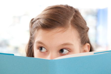 girl reading book: Girl reading a book at school and looking up Stock Photo