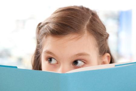 ni�os leyendo: Muchacha que lee un libro en la escuela y mirando hacia arriba