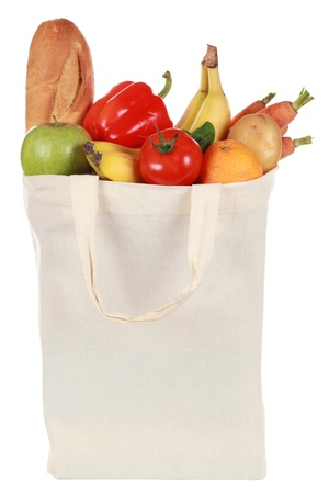 Reusable bag with groceries including a bread, fruits and vegetables, isolated on white photo