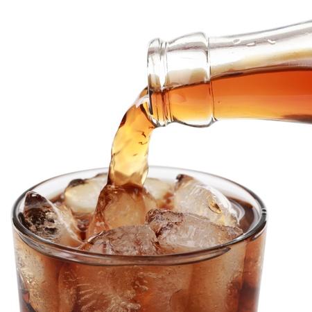 bebidas frias: Cola se vierte de una botella en un vidrio, aislado en blanco
