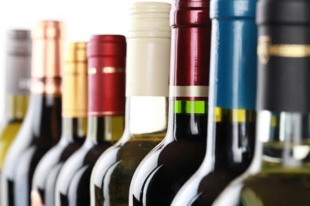 Wijnflessen in een rij geïsoleerd op een witte achtergrond Stockfoto