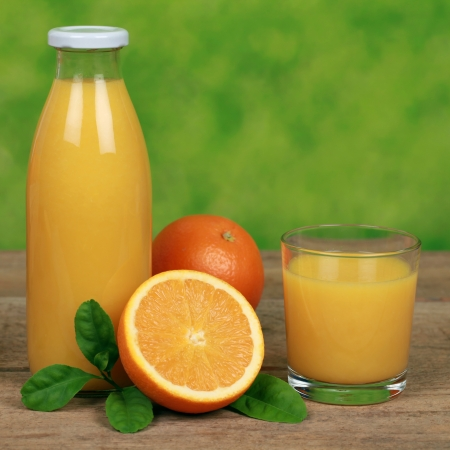Fresh oranges and orange juice on a wooden table Stock Photo - 18933574
