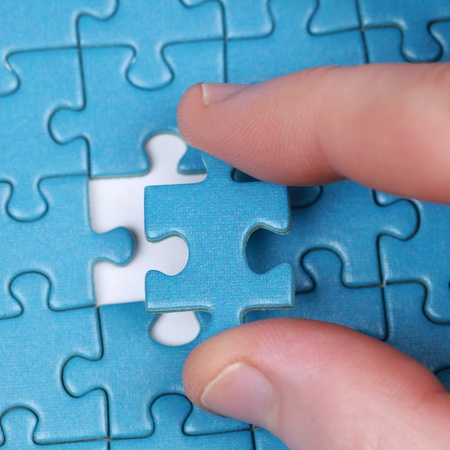 complete solution: Hand putting the last piece of puzzle in a gap