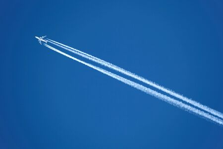 An Airplane with contrail high in the sky photo