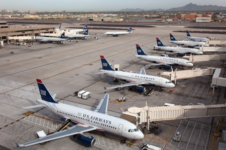 headquartered: Phoenix, Arizona - March 20, 2013: Morning rush of US Airways aircraft at Phoenix Sky Harbor Airport (PHX) in Arizona. US Airways is a major U.S. airline, headquartered in Tempe, Arizona. It operates with 644 aircraft and carried more than 51 million pass