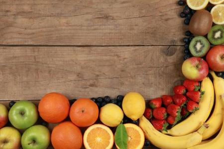 naranjas: Las frutas como las naranjas, los plátanos, las manzanas y los limones en una tabla de madera Foto de archivo