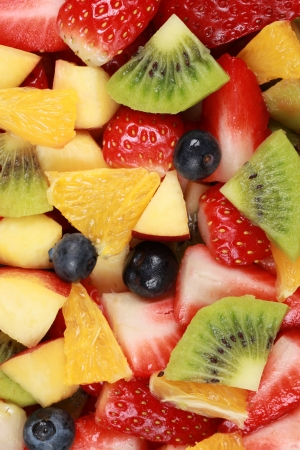 fruit salad: Fruit salad background with strawberries, oranges, kiwi, blueberries and peaches