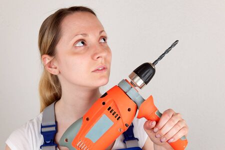 doityourself: Young woman holding a drilling machine, do-it-yourself topic