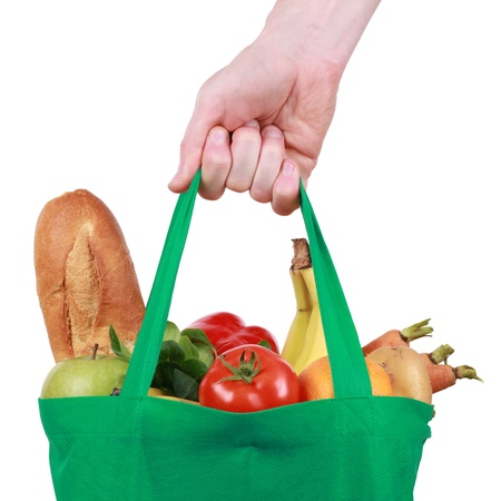 Mano que sostiene un bolso de compras reutilizable llena de frutas y verduras, aislados en blanco