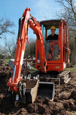 digger: Worker sitting in an excavator in a garden Stock Photo