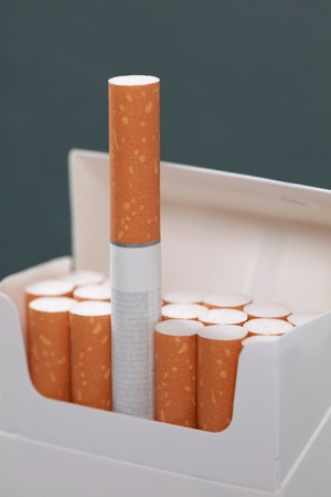 Closeup of a pack with cigarettes, one cigarette standing out of the crowd photo