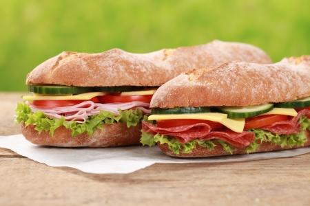 bocadillo: Baguettes con salami, jam�n, queso, tomate, lechuga y pepino Foto de archivo