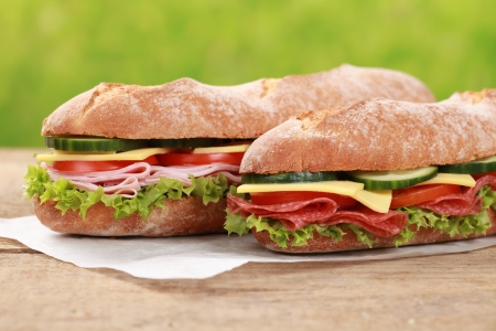 Baguettes with salami, ham, cheese, tomatoes, lettuce and cucumber Stock Photo