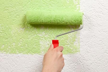 house painter: Un pintor es la celebraci�n de un rodillo de pintura en la mano y pinta una pared Foto de archivo