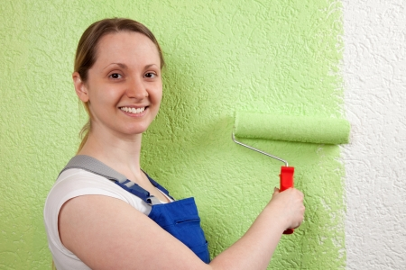 Young woman painting a wall with a paint roller Stock Photo - 20679560