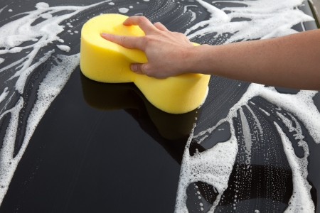 Washing a car with a sponge and soap