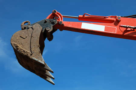 Raised scoop of an earth mover over blue sky photo