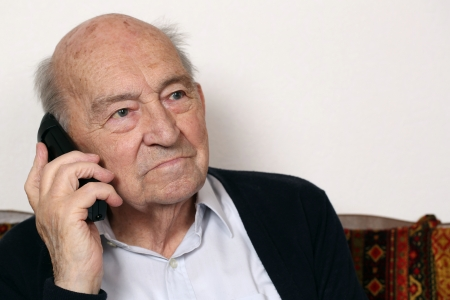 old phone: Portrait of an old senior man with a telephone Stock Photo