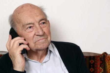 Portret van een oude senior man met een telefoon
